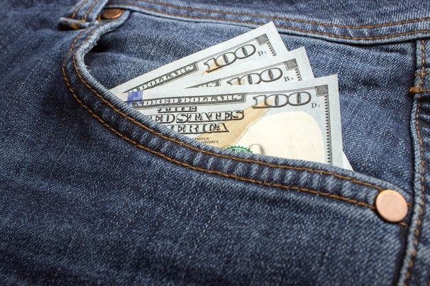 Dollar banknotes in jeans pocket closeup.