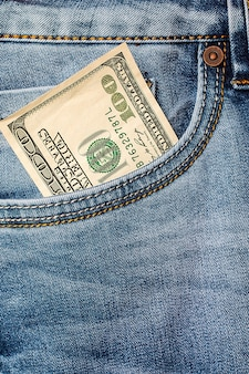 Dollar banknotes in jeans pocket