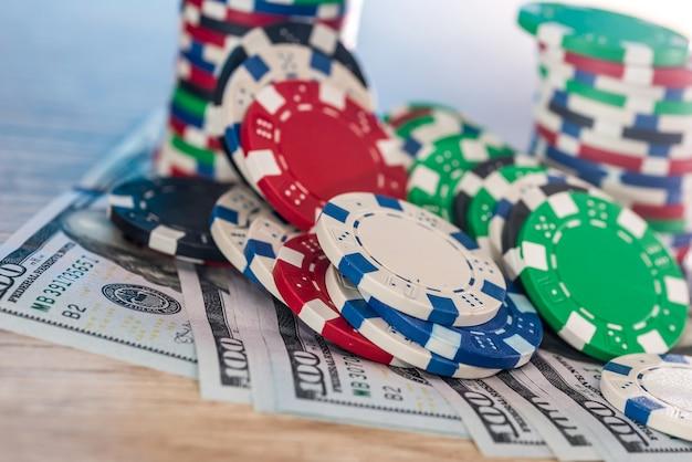 카지노 칩이 있는 나무 테이블에 있는 달러 지폐