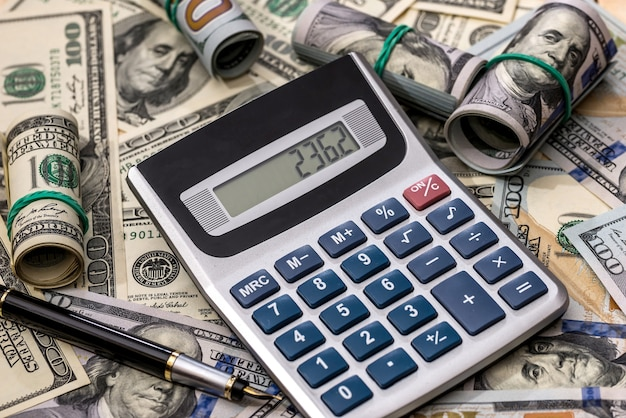 Dollar banknotes, pen and calculator