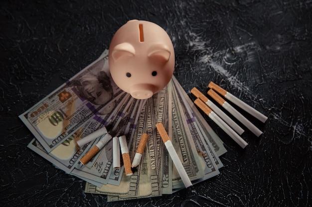 Банкноты доллара розовая копилка и сигареты на сером столе дорогая и вредная привычка