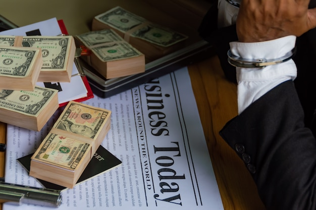 Dollar banknotes placed on the newspaper and businessmen was handcuffed.