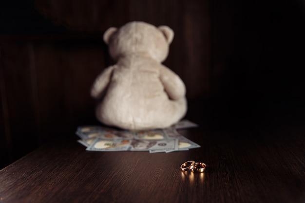 木製のテーブルにドル紙幣、指輪、テディベア。離婚と扶養手当の概念。