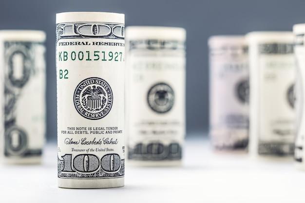 Банкноты доллара катятся в других положениях американская валюта на белой доске и расфокусированном фоне