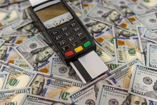 Dollar banknotes and terminal with credit card