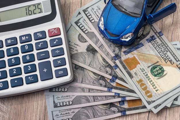 계산기와 장난감 자동차가 있는 달러 지폐