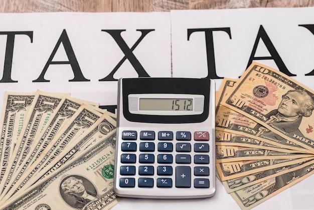 단어 '세금'에 계산기와 달러 지폐