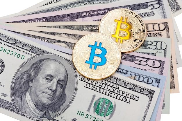 Долларовые банкноты с золотыми биткойнами синего и желтого цвета криптовалюты на белом фоне. фотография высокого разрешения.