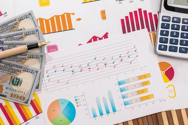 펜과 계산기 비즈니스 그래프에 달러 지폐