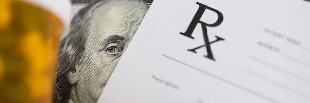 Долларовая банкнота и рецепт врачей лежат на столе врачей в клинике крупным планом