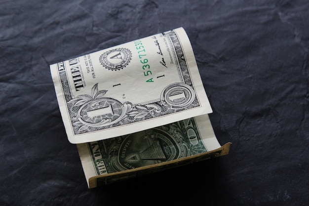 Долларовая банкнота на черной поверхности