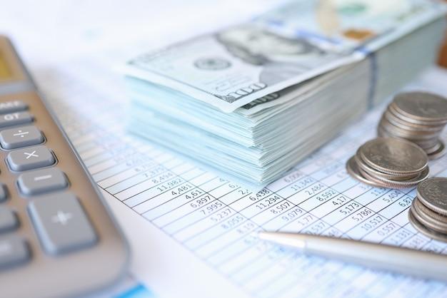 数字のクローズアップで文書に横たわっているドル紙幣と硬貨。違法な会計概念