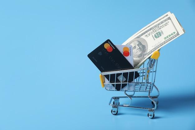 Купюры и кредитные карты в корзине на покупки, изолированных на синем