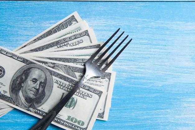Долларовые купюры и вилка на столе