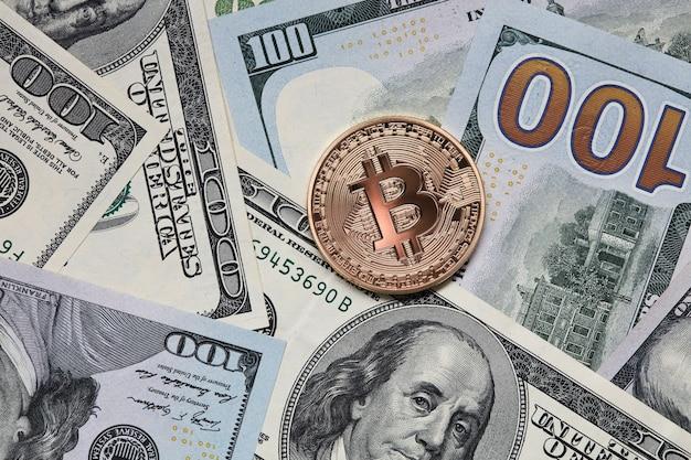 Долларовые купюры и золотая монета биткойн