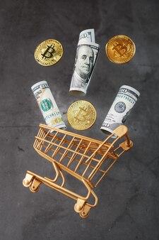 ドル紙幣とitkonコインが暗い表面のゴールデンバスケットから飛び出しました