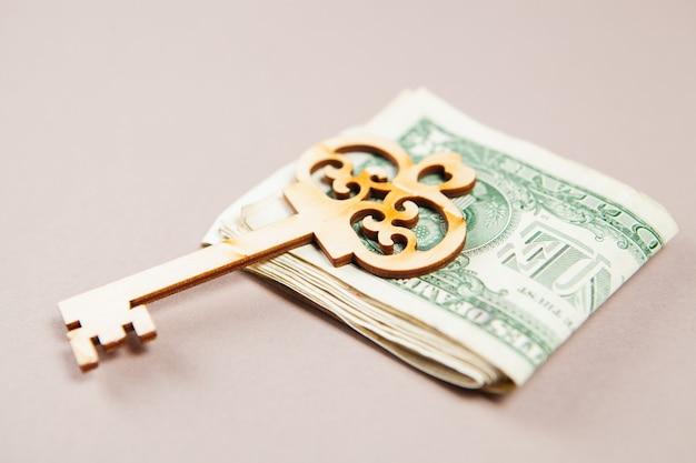 Долларовые купюры и ключ на столе