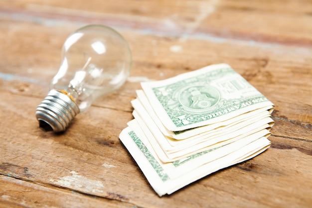 달러 지폐와 전구 나무 테이블에