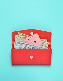 Dollar bills, audio cassette in a red leather purse on a blue pastel background. top view