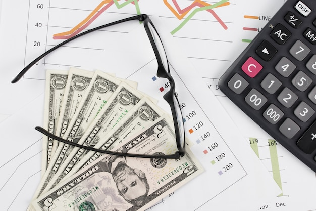 Dollar bills, calculator and glasses on graph background.