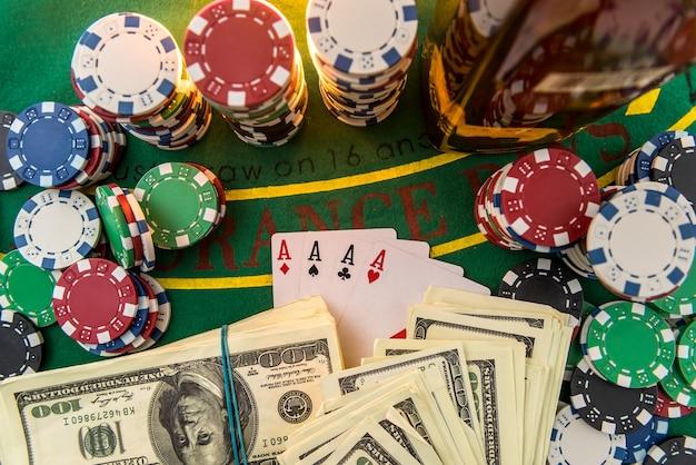 달러 지폐, 카지노 칩 및 테이블에 위스키 유리. 도박 게임 및 엔터테인먼트 개념.