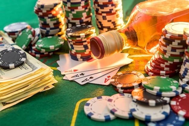 ドル札、カジノチップ、テーブルの上のウイスキーグラス。ギャンブルゲームとエンターテイメントのコンセプト。