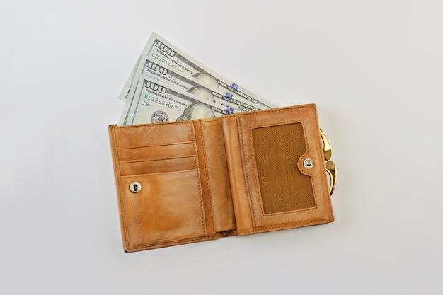 Долларовые купюры в коричневом кожаном кошельке на сером фоне