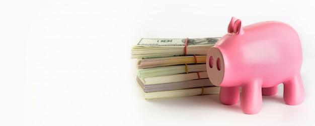 Купюры в пачках на белом фоне. рядом находится копилка в виде розовой свиньи. баннер.