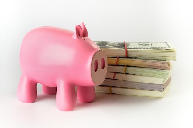 Купюры в пачках на белом фоне. рядом находится копилка в виде розовой свиньи.