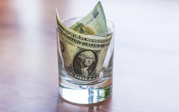 木製のテーブルの上のガラスの瓶のドル札。お金の節約の概念