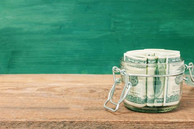 木製のテーブルの上のガラスの瓶のドル札。お金の節約の概念。