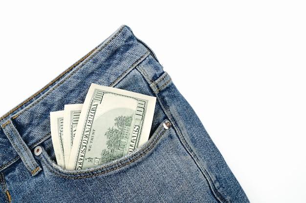 Долларовые банкноты в переднем кармане джинсов, на изолированном белом фоне. фото высокого качества