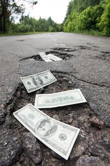 道路のくぼみにドル札