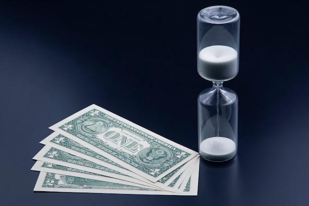 달러 지폐는 모래 시계 근처에 놓여 있습니다. 시간은 돈이다. 월급. 적시에 비즈니스 솔루션.