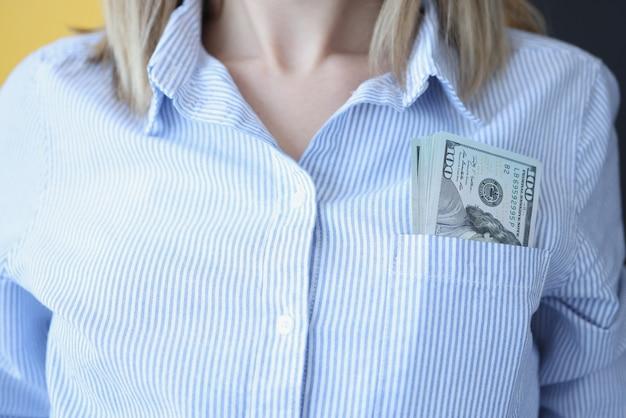 女性のシャツのポケットのクローズアップに横たわっているドル札。詐欺と贈収賄の概念