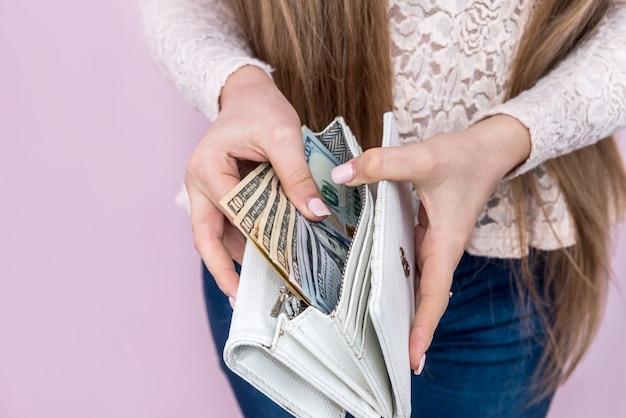 여성의 손에 의해 지갑을 벗고 달러 지폐