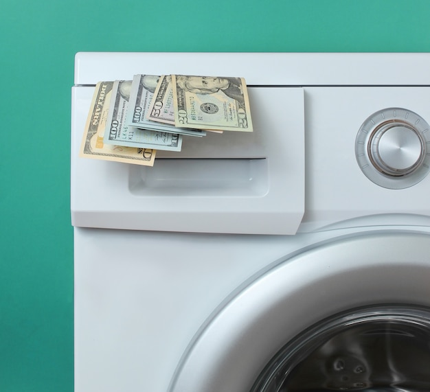 Dollar bills in the washing machine against blue background. expensive wash concept