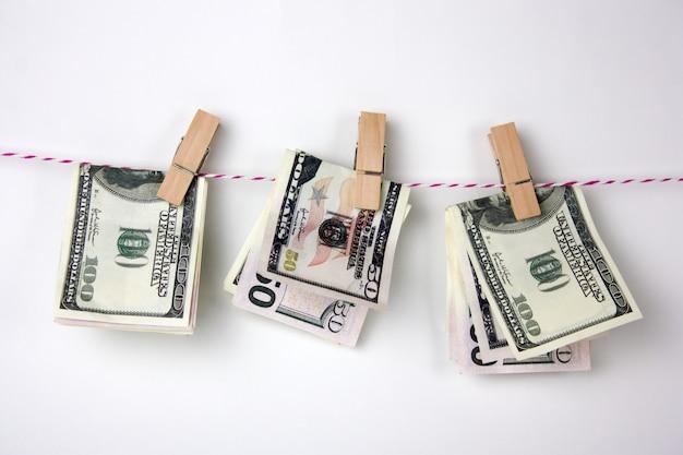 Clothespins와 달러 지폐는 밧줄에 걸으십시오