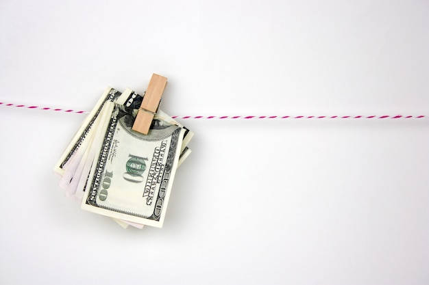 Dollar bills with clothespins hang on a rope