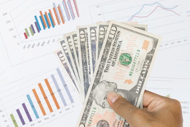 Долларовые купюры с диаграммой и финансовой диаграммой.