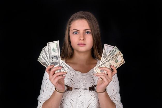 Долларовая взятка разделена в руках женщины в наручниках