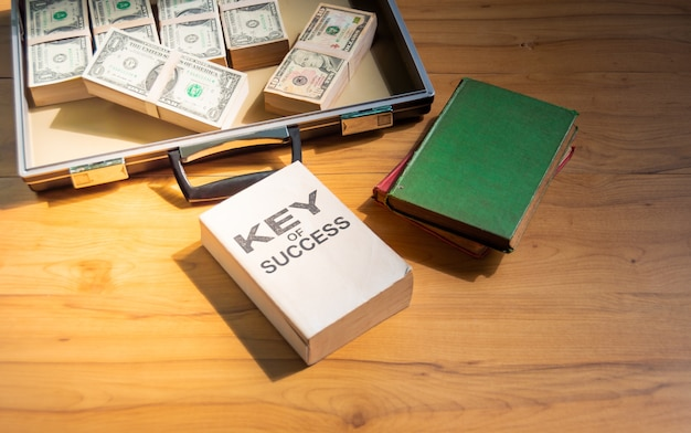 Dollar in briefcase, old book and guide to success on wooden table, to business concept.