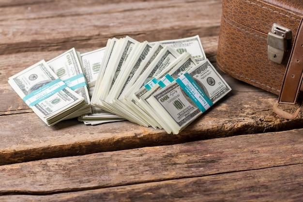 Пачки долларов и коричневый футляр. наличные деньги на старом деревянном фоне. управляйте своими деньгами с умом. доход будет расти.