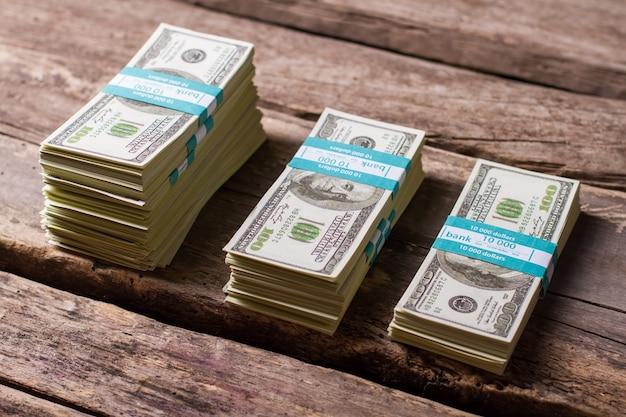 나무 배경에 달러 번들입니다. 다른 크기의 현금 스택. 열심히 일해서 얻은. 오래 된 테이블에 돈 절약입니다.