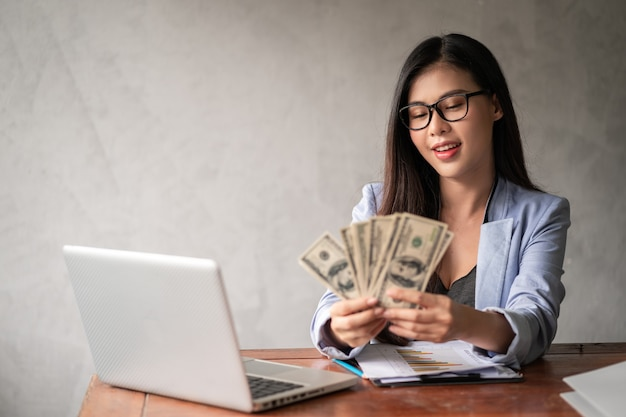Dollar in a businesswoman hand. an asia woman is working from home or office and glad to get dollar money from work and from a supplementary career or part-time self-employment.