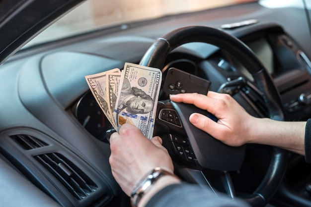 Dollar and car key in male's hand inside car. pay in goods or rent car