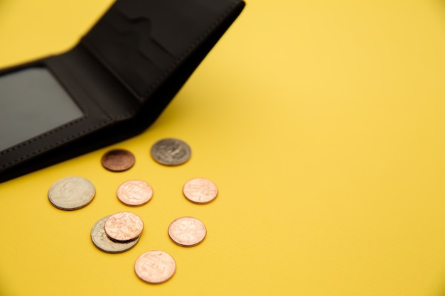 Dollar coins spilling out of open grey leather wallet.