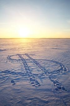 雪の上に描かれたドル通貨のアイコン。バックグラウンドでの夕日。