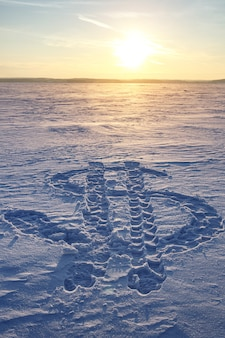 Dollar currency icon drawn on the snow. sunset in the background.