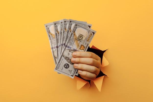 Долларовая валюта в руке, держащей долларовые банкноты через отверстие в желтой бумаге крупным планом